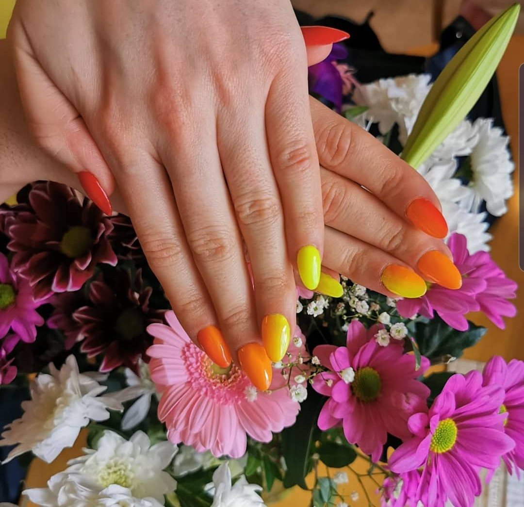 Orange & Yellow Painted Nails over pink flowers